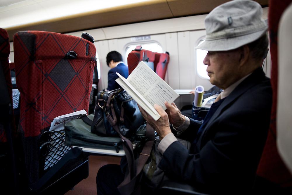TOKYO, JAPAN - DECEMBER 21 : A man reads a book inside of a bullet train at Tokyo Station on December 21, 2015, Tokyo, Japan.<br />   <br /> Photo: Richard Atrero de Guzman