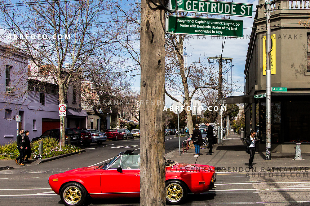 A red sports car drives down Gertrude Street in Melbourne, Australia, September 1, 2017. For much of the 20th century Gertrude Street and the surrounding Fitzroy area was a working class suburb, today it has become gentrified and a very popular area among young professionals as well as culinary tourists. Asanka Brendon Ratnayake for the New York Times