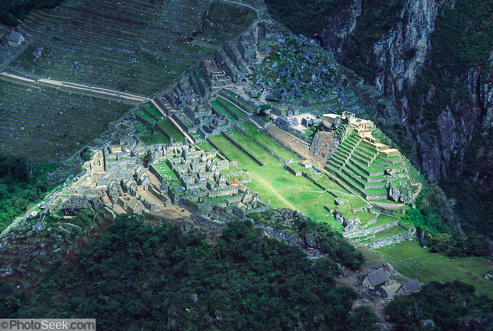 "From atop the peak of Huayna Picchu, see terraces of the Machu Picchu archeological site in the Cordillera Vilcabamba, Andes mountains, Peru, South America. The Incas built temples, terraces, and a trail up the peak of Huayna Picchu (""Young Peak"" in Quechua, 2720 meters or 8920 feet above sea level). Machu Picchu was built around 1450 AD as an estate for the Inca emperor Pachacuti (14381472). Spaniards passed in the river valley below but never discovered Machu Picchu during their conquest of the Incas 1532-1572. The outside world was unaware of the ""Lost City of the Incas"" until revealed by American historian Hiram Bingham in 1911. Machu Picchu perches at 2430 meters elevation (7970 feet) on a well defended ridge 450 meters (1480 ft) above a loop of the Urubamba/Vilcanota River ( Sacred Valley of the Incas). UNESCO honored the Historic Sanctuary of Machu Picchu on the World Heritage List in 1983."