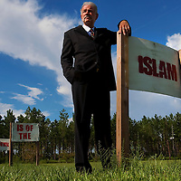 "GAINESVILLE, FL -- August 18, 2010 -- Pastor Terry Jones poses for a portrait with signs that state ""Islam is of the Devil"" at the Dove World Outreach Center in Gainesville, Fla., on Wednesday, August 18, 2010.  The church is planning on burning multiple copies of the Koran on the anniversary of the September 11th terrorist attacks.  (Chip Litherland for The New York Times)"