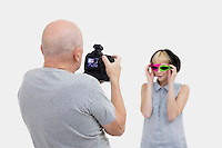 Senior photographer taking a photograph of fashion model during photo shoot