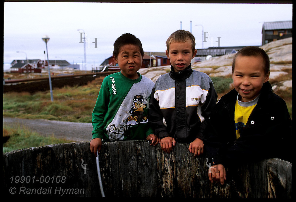 Three Greenlandic boys pose by wooden vat outside Knud Rasmussen Museum, birthplace of famed explorer; Ilulissat, Greenland.