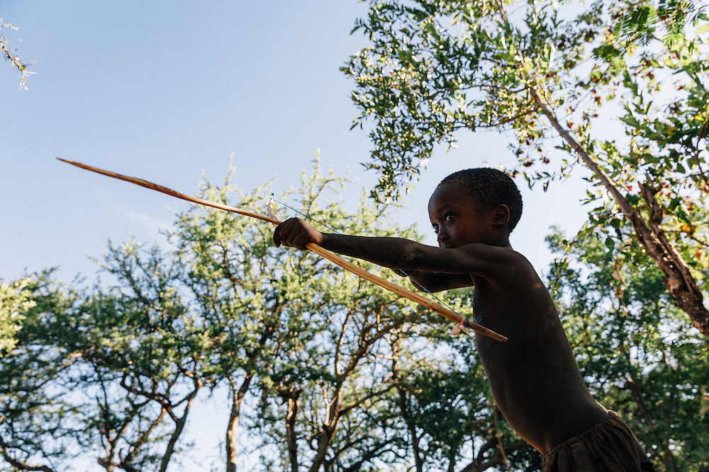 A young Hadza boy, Koyobe, 5,practices with his bow and arrow in camp, boys are taught to hunt from a very young age and start with wildlife around the camp, such as lizards, before joining bigger hunts as they grow older. Yaeda valley area in Northern Tanzania. Photo by Greg Funnell, March 2016.