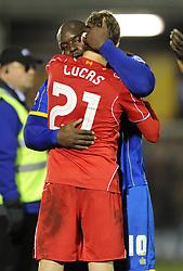 Wimbledon's Adebayo Akinfenwa hugs Liverpool's Lucas Leiva - Photo mandatory by-line: Dougie Allward/JMP - Mobile: 07966 386802 - 05/01/2015 - SPORT - football - London - Cherry Red Records Stadium - AFC Wimbledon v Liverpool - FA Cup - Third Round