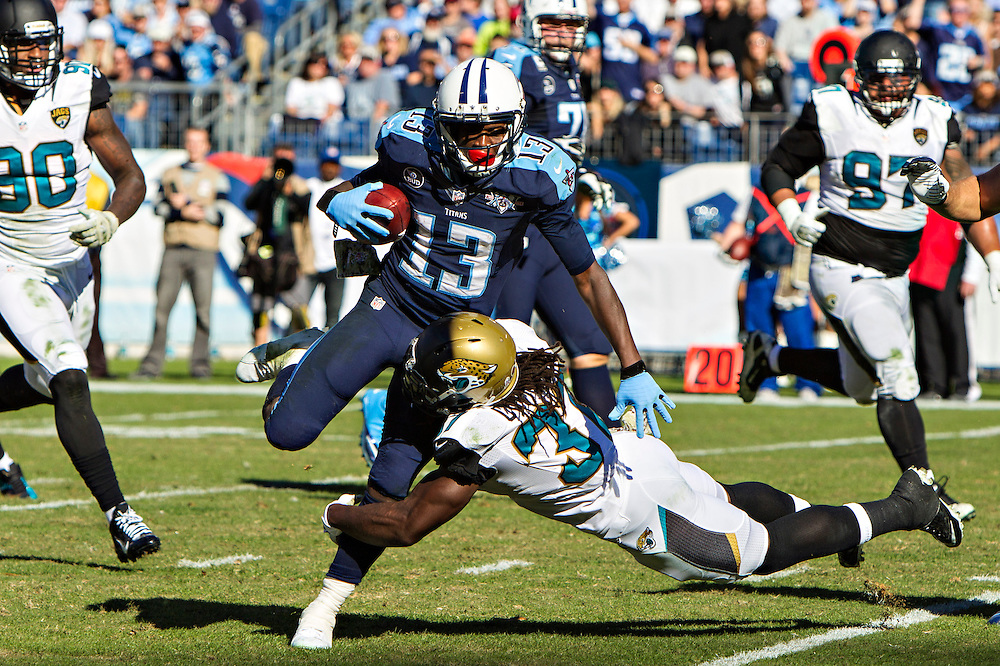 NASHVILLE, TN - NOVEMBER 10:  Kendall Wright #13 of the Tennessee Titans is tackled by Johnathan Cyprien #37 of the Jacksonville Jaguars at LP Field on November 10, 2013 in Nashville, Tennessee.  The Jaguars defeated the Titans 29-27.  (Photo by Wesley Hitt/Getty Images) *** Local Caption *** Kendall Wright; Johnathan Cyprien