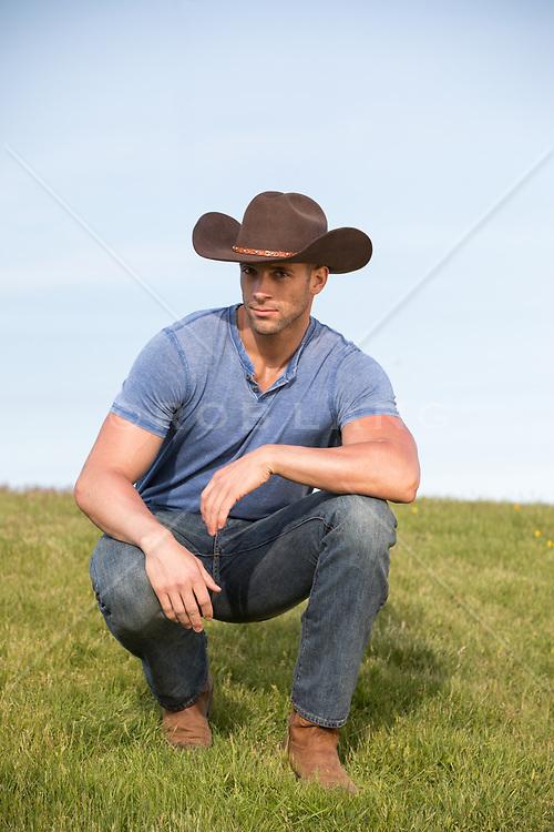 cowboy squatting on a grassy  hillside