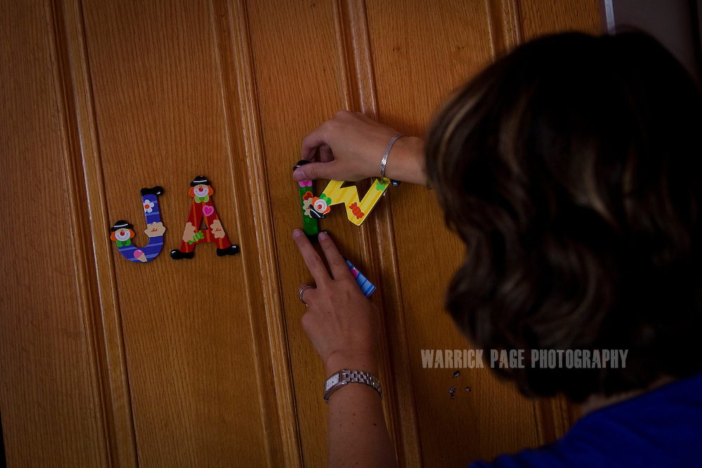 Eva Vildosola puts the name of her son Jamie on his bedroom door as she unpacks the remainder her family's belongings in their new home, on September 1, 2012, in Buckden, England. The Spanish family immigrated to England due to the ongoing economic crisis that has impacted heavily on Spain. (Photo by Warrick Page)