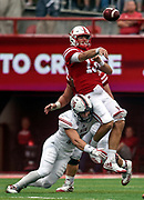 Nebraska Cornhuskers quarterback Tanner Lee (13) is knocked off his feet by Northern Illinois Huskies defensive end Sutton Smith (15) while completing a pass to Nebraska Cornhuskers wide receiver Stanley Morgan Jr. (8) during a game on Saturday at Memorial Stadium in Lincoln. (Matt Gade / Republic)