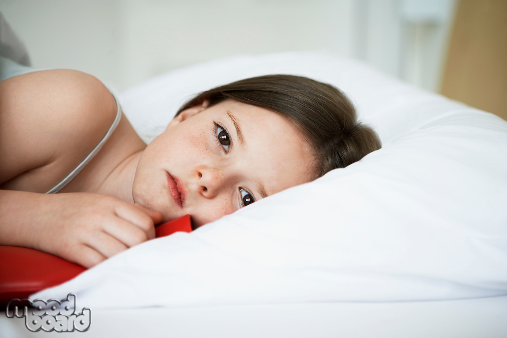 Little girl with cold in bed holding hot water bottle portrait close up