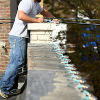 Adam Robison | BUY AT PHOTOS.DJOURNAL.COM<br /> Justin White, an employee for Tupelo Public Works Department, changes bulbs on the roof line lights above Rogers Realty and appraisal Company and the Down on Main Street Association Office on Broadway Street Monday afternoon in Tupelo.