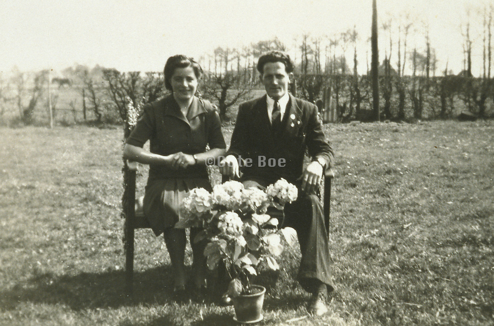 vintage photograph of couple seated on bench in field