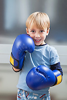 Portrait of Caucasian boy in casuals wearing boxing gloves