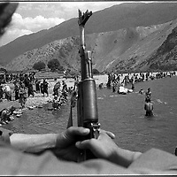 A mujehadin watches over Taliban prisoners out for a swim in the Panshir, Afghanistan. (Greg Marinovich)