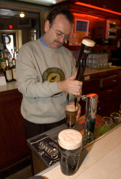 Cormac Ronan, owner of the Irish Times in Laurium, Mich. pours a pint of Guinness beer and etches a shamrock in the beer's frothy head.