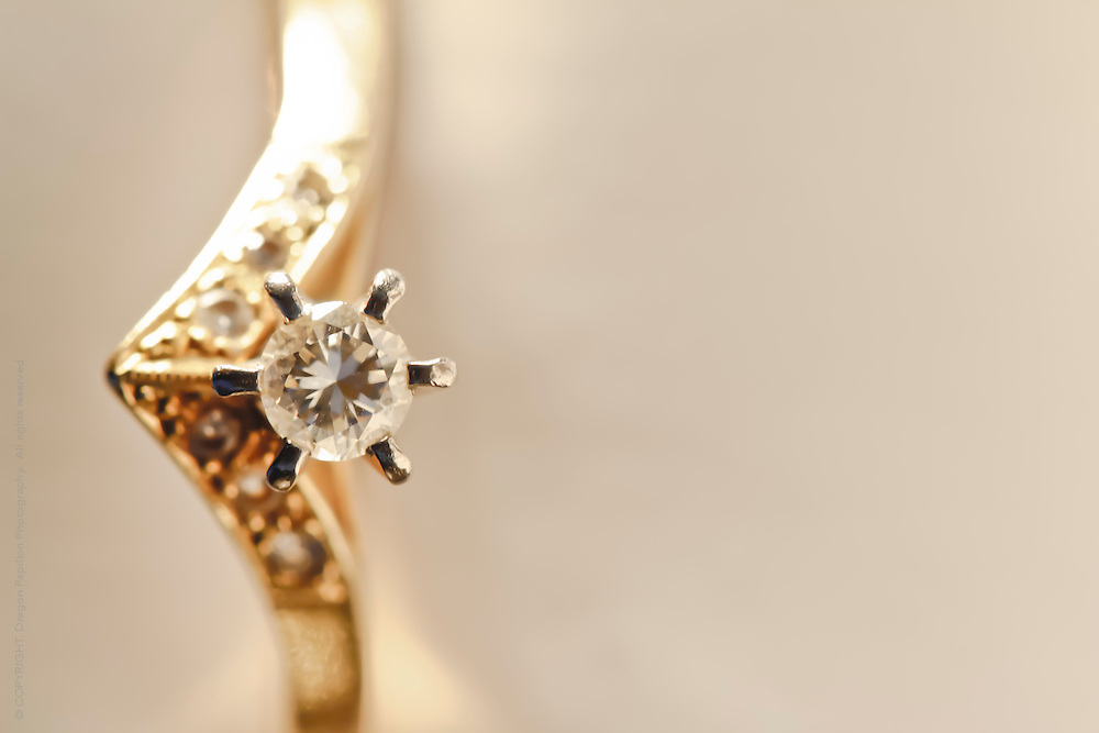 gold ring with diamonds against creamy background