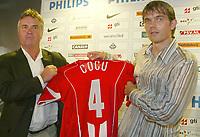 Fotball<br /> Barcelona-spilleren Phillipe Cocu har skrevet under for PSV Eindhoven. Her poserer han med sin nye drakt sammen med PSV-trener Guus Hiddink.<br /> 7. juni 2004<br /> Foto: Digitalsport<br /> NORWAY ONLY