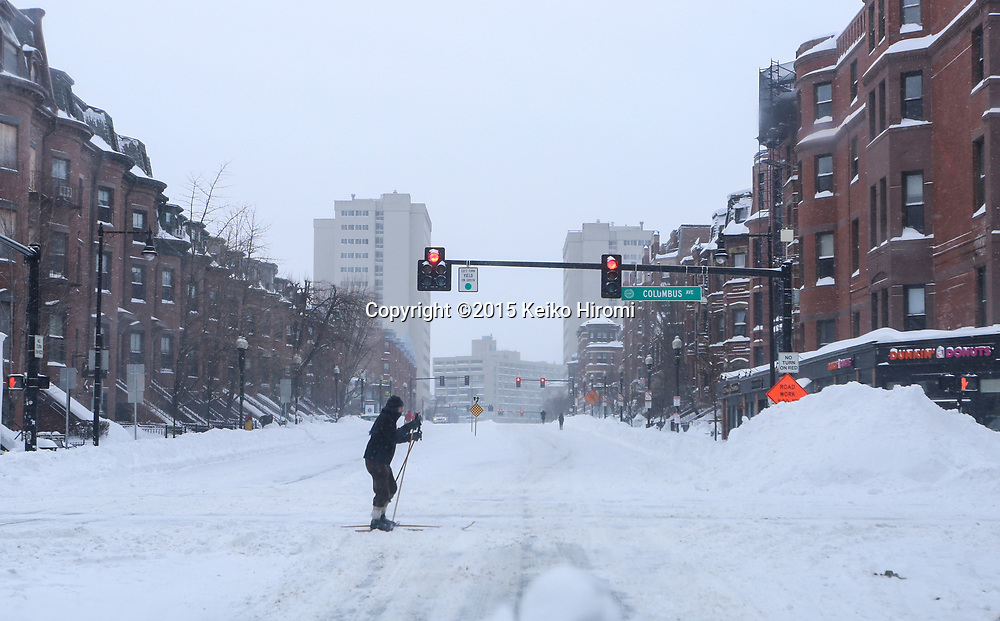 January 27 2015, Boston, MA USA: A skier crossing on Massachusetts Avenue in South End neighborhood of Boston, in Boston, MA.  Massachusetts was pounded by snow and lashed by strong winds early Tuesday as bands of heavy snow left some towns including Sandwich on Cape Cod and Oxford in central Massachusetts reporting more than 18 inches of snow.