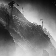 A mist and fog enshrouded coastline gives way to a lone residence and the Pacific Ocean near Cannon Beach Oregon.