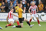 Chris Hussey shoots past Liam O'Neil and almost sores  during the EFL Sky Bet League 2 match between Cambridge United and Cheltenham Town at the Cambs Glass Stadium, Cambridge, England on 25 August 2018.