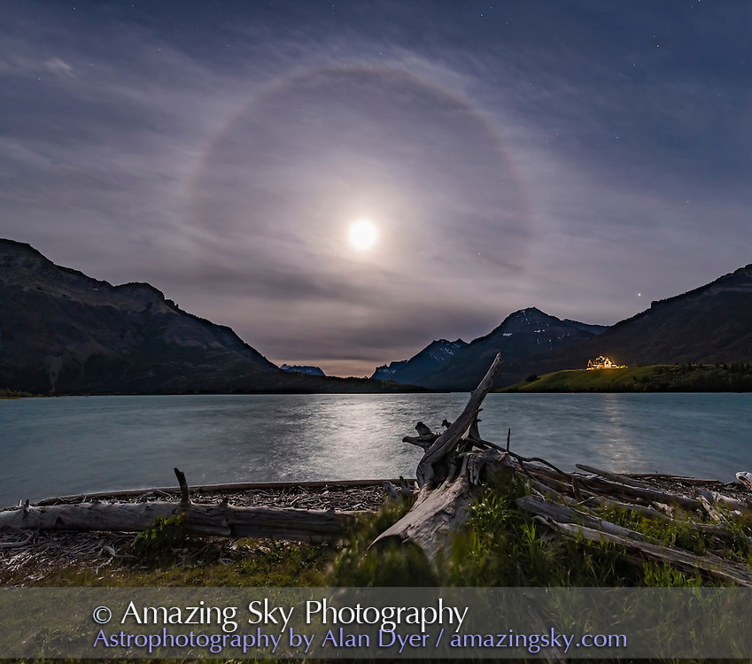 An ice crystal halo around the Full Moon on solstice eve, June 19, 2016, from Driftwood Beach at Waterton Lakes National Park, Alberta. Mars is the bright object at far right, Saturn is just right of the Moon. The iconic Prince of Wales Hotel is below Mars.<br /> <br /> This is a 3 panel vertical panorama, each panel with the 20mm Sigma lens at f/4 for 5 seconds at ISO 800. Stitched in ACR.