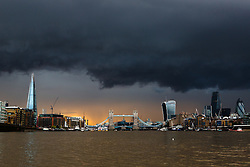 © Licensed to London News Pictures. 12/08/2014. London, UK. Black clouds are seen over Tower Bridge and the City of London skyline shortly before a heavy rain shower and sunset this evening. Photo credit : Vickie Flores/LNP
