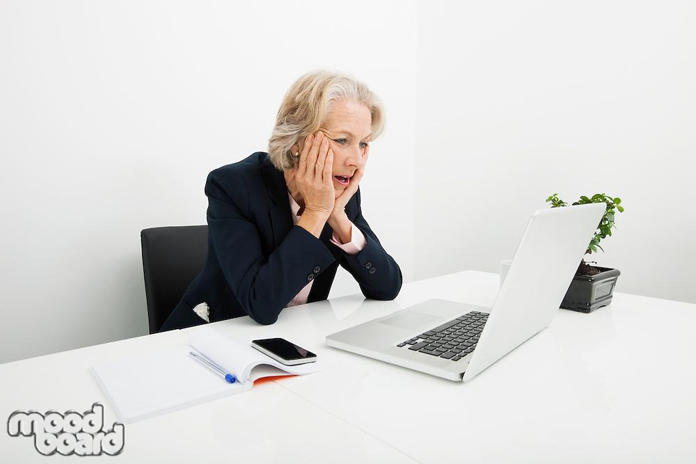 Shocked senior businesswoman using laptop at desk in office
