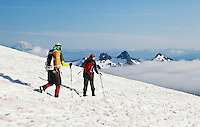 Climbers descending Mount Rainier with Mount Adams and the Tatoosh range in the background. Washington, USA.
