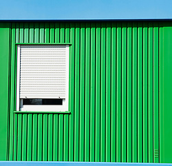 Bright green steel building with window and shutter