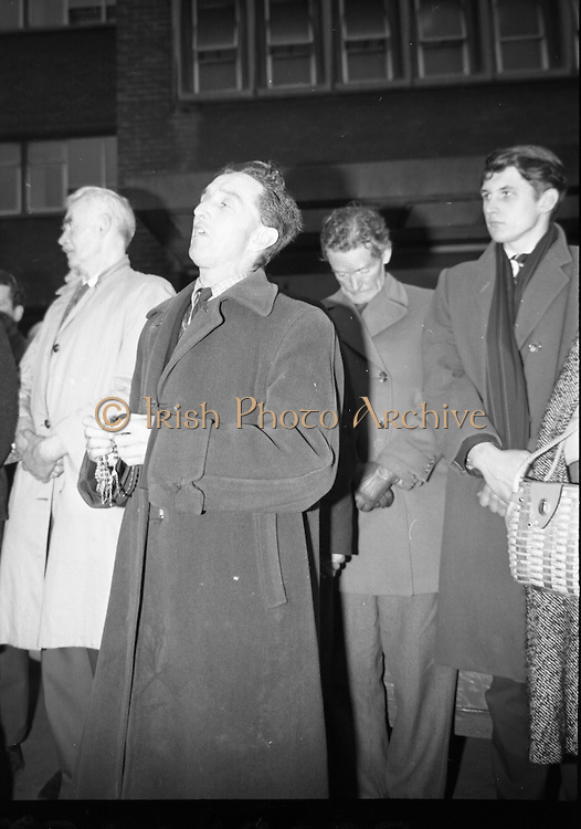 A Dubliner leads the recitation of the Rosary outside the Meath Hospital, as the remains of Brendan Behan are removed..21.03.1964