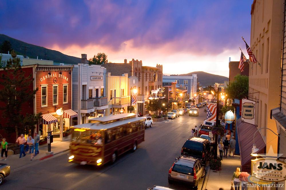 colorful rain clouds over setting sun looking down Main Street, Park City, Utah USA