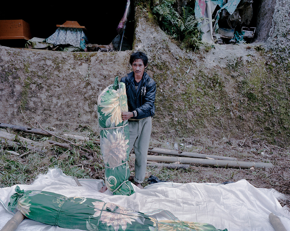 A family member poses for a portrait after adding a new layer of fabric to wrap the remains of a relative in Barrupu. In this district of Toraja, the body is not buried but placed in a hole carved into a cliff. <br /> <br /> Ma'nene is a tradition that takes place in August after harvest where the bodies of the dead loved ones are exhumed to be cleaned, groomed and dressed. For most, it's a bittersweet moment, a chance to reunite and physically see and touch and reconnect with loved ones who had passed on.