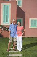 Portrait of senior couple in front of house
