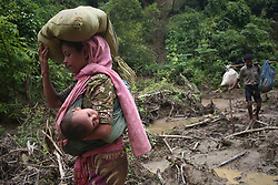 September 5, 2017 - Cox'S Bazar, Bangladesh - A rohingya woman carries her child in a sling while  walks through in hill after crossing the border into Bangladesh near cox's bazar area, teknaf.  A total of 87,000 mostly Rohingya refugees have arrived in Bangladesh since violence erupted in neighbouring Myanmar on August 25, the United Nations said today, amid growing international criticism of Aung San Suu Kyi. Around 20,000 more were massed on the border waiting to enter, the UN said in a report. (Credit Image: © Mushfiqul Alam/NurPhoto via ZUMA Press)