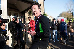 © Licensed to London News Pictures. Prime Minister DAVID CAMERON with his medal after the race. British Prime Minister DAVID CAMERON taking part in The Great Brook Run in Chadlington, Oxfordshire on December 29, 2014. The cross-country course, which is over a mile long, takes competitors through muddy fields, through cold water and under 3-foot wide tunnel. Photo credit : Ben Cawthra/LNP