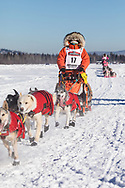 Musher Kristin Bacon competing in the 45rd Iditarod Trail Sled Dog Race on the Chena River after leaving the restart in Fairbanks in Interior Alaska.  Afternoon. Winter.