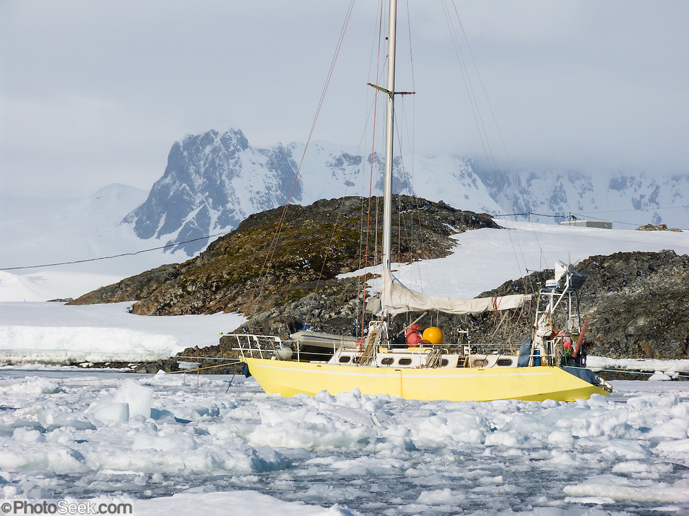 "A hardy yellow sailboat anchors amid sea ice at Vernadsky Research Base (Akademik Vernadsky), a Ukrainian Antarctic Station at Marina Point on Galindez Island in the Argentine Islands, Antarctica. The United Kingdom first established research here as Base F or ""Argentine Islands"" on Winter Island in 1947, then built a larger hut on Galindez Island in 1954, renamed it Faraday Station in 1977, and shocked the scientific community by discovering the Antarctic ""ozone hole"" in 1985. The base was transferred to Ukraine in 1996."