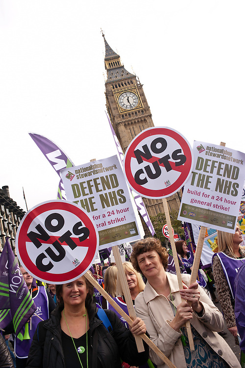 London, UK - 20 October 2012: two women hold signs reading 'No Cuts' and 'Defend the NHS' during the TUC-organised march 'A future that works' against austerity cuts in central London.