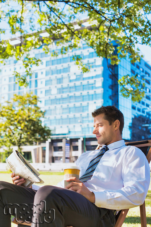 Portrait of handsome businessman drinking coffee and reading newspaper while sitting on folding chair in park