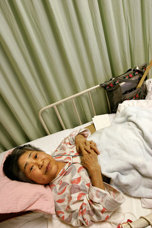 """SUZUKO NUMATA: Pictured in hospital, where she is being treated for osteoporosis.  Numata was 20 and engaged to be married when the bomb fell and shattered her left leg.  Three days later it began to fester and was amputated below the knee, without anesthetic. She later learned that her fiancé had been killed.  She never married and spent her life teaching and unable to talk about what happened until she retired twenty years ago.  """"We used to chant during the war: Be united in one mind like a fireball, 100 million people. Then when the bomb fell the trucks came around and ignored women and children, and just helped the healthy men.  That's when I first understood what war was."""""""