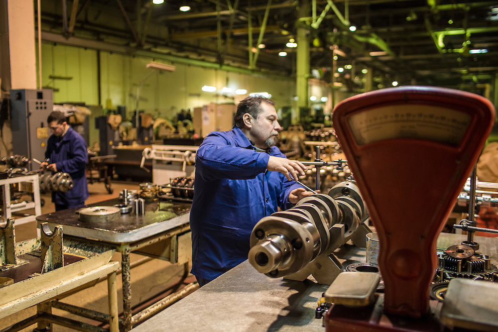 Serhie Grigorovych, 50, and his son Oleksandr Grigorovych, 26, left, at work at the Malyshev Tank Factory on Wednesday, February 11, 2015 in Kharkiv, Ukraine.