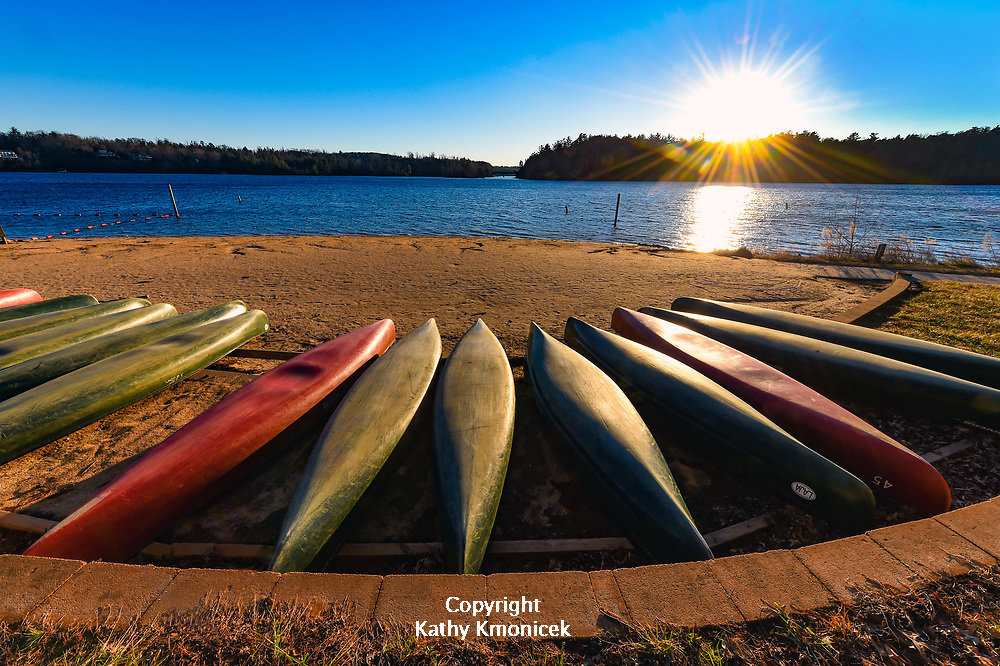 Canoes stored on the beach at Lake James State Park Paddy's Creek, reflect the warmth of the winter sun as it sets in Nebo, North Carolina<br />