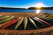 Canoes stored on the beach at Lake James State Park Paddy's Creek, reflect the warmth of the winter sun as it sets in Nebo, North Carolina<br /> <br /> &copy; Photography by Kathy Kmonicek