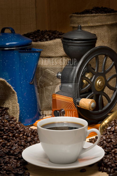 Coffee cup propped with coffee pot, coffee beans, burlap bags of coffee and a vintage coffee grinder