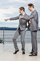Businessmen pointing at something against sky