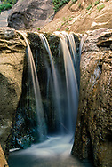 Small waterfall passing over polished sandstone that has a golden hue, Orderville Canyon, © 1990 David A. Ponton