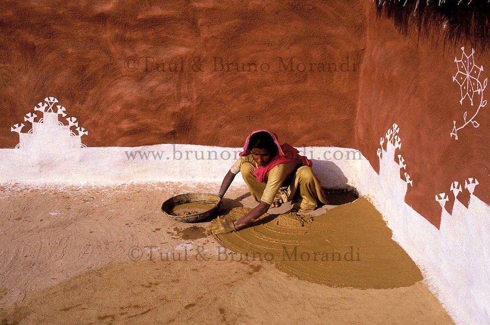 Inde, Rajasthan, Village peint des environs de Jaisalmer, Femme enduisant la cour de sa maison // India, Rajasthan, village around Jaisalmer