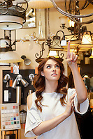 Beautiful young woman pointing finger up in lights store