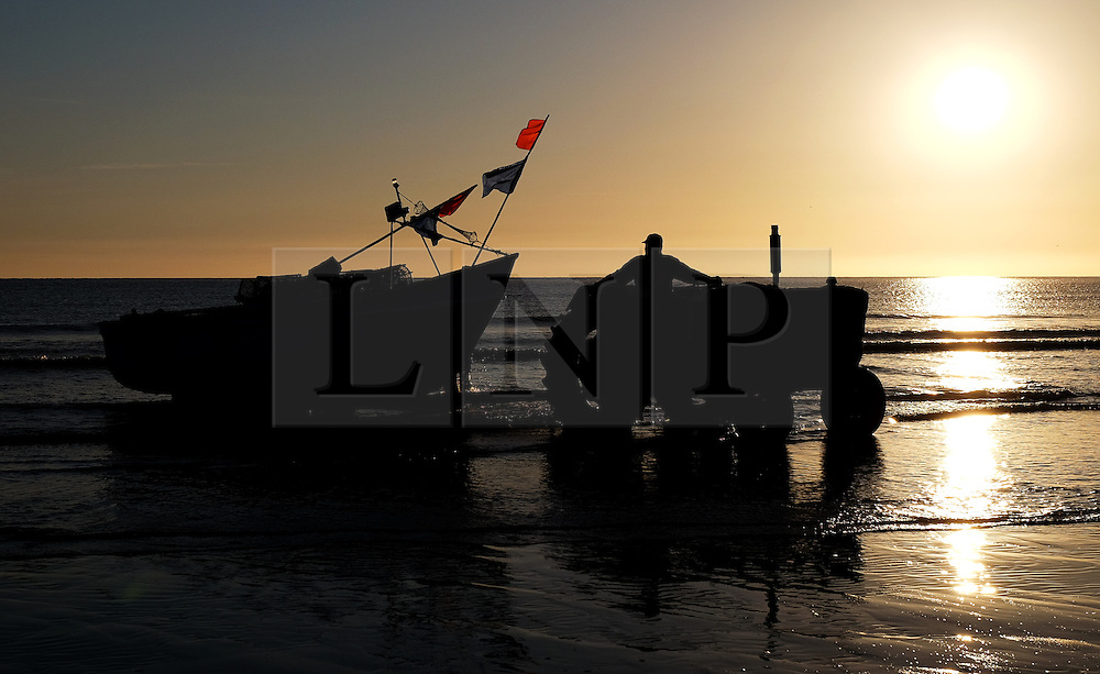 © Licensed to London News Pictures.12/06/15<br /> Saltburn by the Sea, England<br /> <br /> The last remaining commercial fishing boat in Saltburn, Ellen, is prepared for launch by her crew as dawn breaks over the beach.<br /> <br /> Photo credit : Ian Forsyth/LNP