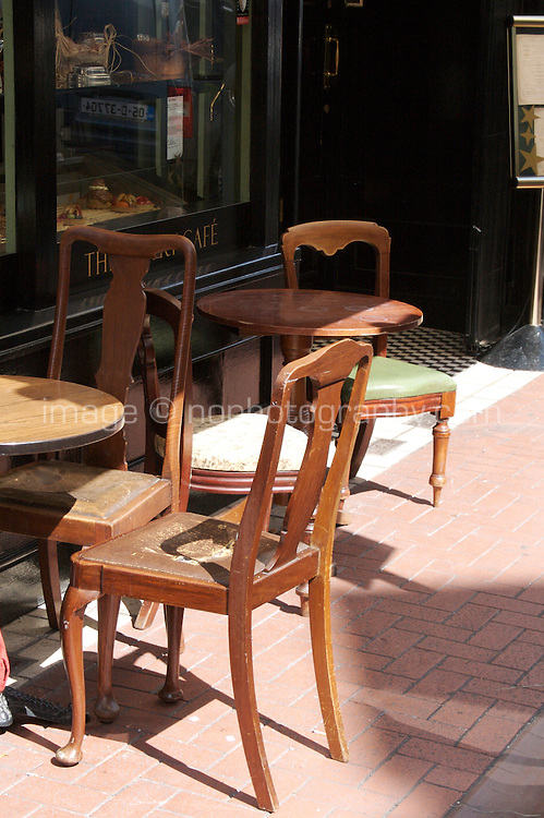 An assortment or antique chairs and tables outside a french style cafe in Dublin Ireland