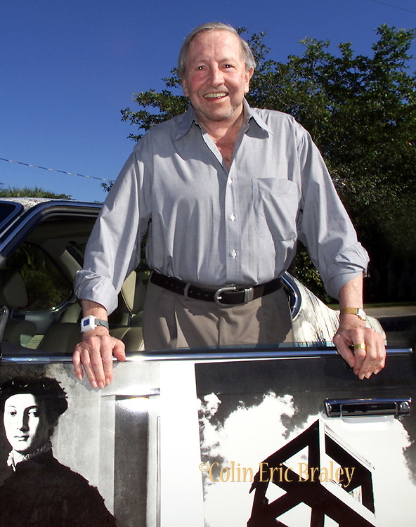 """American pop culture artist Robert Rauschenberg poses next to one of his """"Beamer"""" collages at an art gallery in Naples, Florida in this July 13, 2002, file photo. The 82-year-old died Monday, May 12, 2008, of heart failure according to Jennifer Joy, his representative at PaceWildenstein gallery in New York. Rauschenberg's incorporation of everyday items, both common place and the odd in his artwork earned him the reputation as a pioneering pop artist, gaining fame in the 1950's. Photo by Colin Braley."""